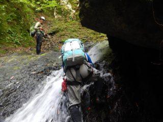 張り出した岩の下に懸かる滝を登る